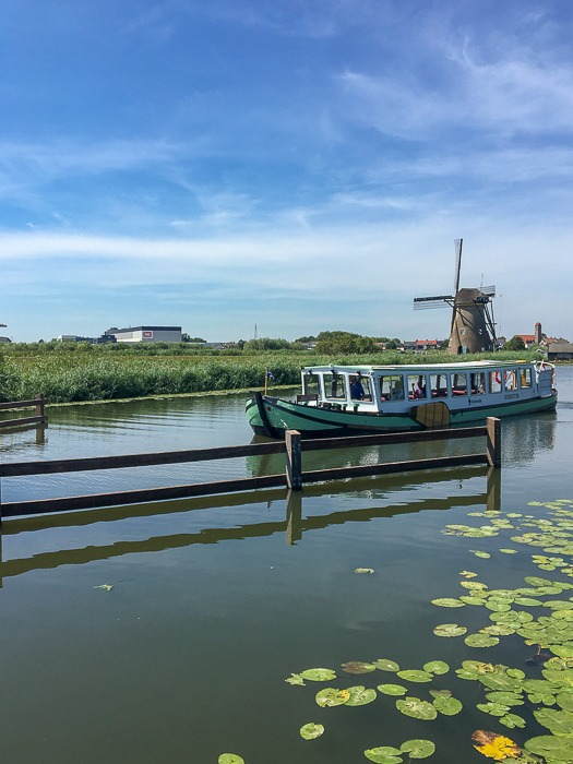 boat on a canal in holland with windmill in background