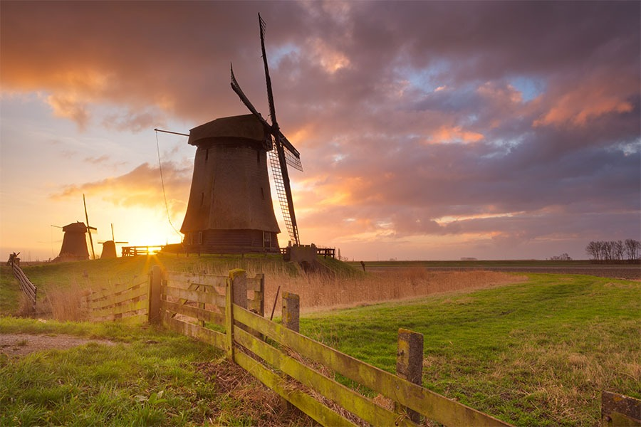 sunrise behind windmills with cloudy sky